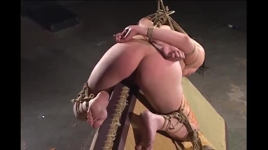 緊縛された娘が身体にロウソクを浴びせられ三角木馬に重り付きで乗せられる拷問SM。鞭で尻を叩かれ悲鳴をあげ涙を流して小刻みに痙攣する。